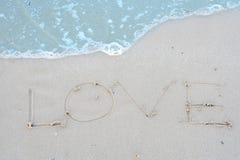 L'amour de mot sur la plage avec la vague Photos libres de droits