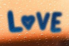 L'amour de mot sur le verre avec la goutte de pluie Images stock