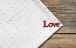 L'amour de mot sur une nappe verte de point de polka Photo stock