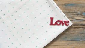 L'amour de mot sur une nappe verte de point de polka Photographie stock