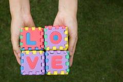 L'amour de mots de puzzle a la prise en main Images stock
