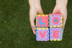 L'amour de mots de puzzle a la prise en main avec le fond vert Photos stock