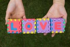 L'amour de mots de puzzle a le fond de prise en main Image libre de droits