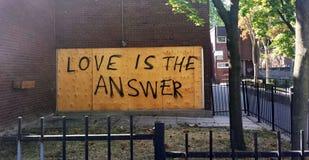 L'amour de phrase est la réponse écrite sur un mur dans le stree Photo libre de droits