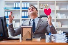 L'amour de sentiment d'homme d'affaires et aimé dans le bureau Image stock