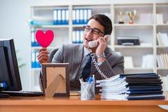 L'amour de sentiment d'homme d'affaires et aimé dans le bureau Photographie stock libre de droits