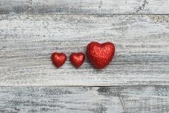 L'amour de trois rouges Shinny des coeurs sur le fond en bois de texture avec le copyspace Jour du `s de Valentine Photographie stock