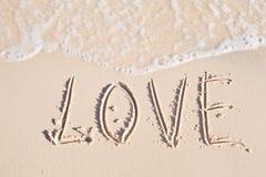 L'amour de Word écrit dessus envoient au bord de la mer Image stock