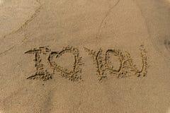 L'amour de Word vous écrit dans le sable sur une plage Photo libre de droits