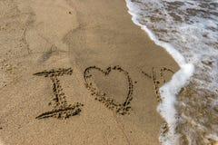 L'amour de Word vous écrit dans le sable sur une plage Photo stock