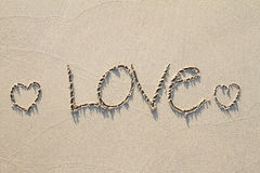 L'amour des textes de dessin et deux coeurs sur le sable échouent avec l'ombre molle Photos libres de droits