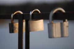 l'amour en acier trois en métal ferme à clef sur la balustrade du pont au-dessus de la rivière Photographie stock libre de droits