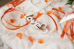 L'amour en bois découpé de mot est à Tulle avec les rubans oranges Images stock