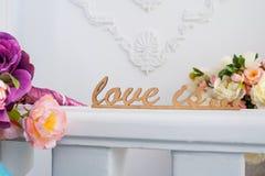 L'amour en bois de mots est avec des fleurs dans le studio Images libres de droits