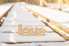 L'amour en bois se connectent de vieux rails dans la neige Images libres de droits