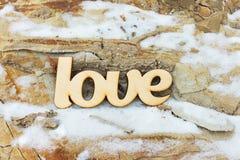 L'amour en bois se connectent la texture en pierre avec la neige Photo stock