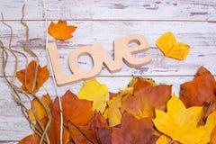 L'amour en bois se connectent le fond en bois blanc minable, avec les feuilles jaunes Concept d'automne Vue supérieure Photo libre de droits