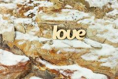 L'amour en bois se connectent le fond en pierre de roche avec la neige Photos stock