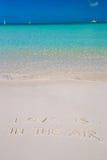 L'amour est dans le ciel écrit sur le blanc tropical de plage Images libres de droits