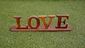 L'amour est dans le ciel et sur le vert - exprimez l'AMOUR étendu sur l'herbe - W Photos stock