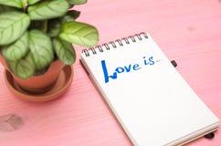 L'amour est inscription en page de papier de bloc-notes Images stock