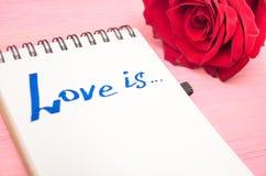 L'amour est inscription en page de papier de bloc-notes et fleur rose Image stock
