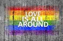 L'amour est tout autour et drapeau de LGBT peint sur le béton gris de texture de fond Photographie stock libre de droits