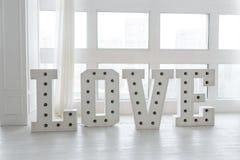 L'amour est un cadeau, jour de Valentine's d'amour Lumière d'ampoule sur la lettre de l'amour Lettre d'amour de lumière de chap Photo stock