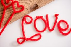 L'amour est un mot est écrit orthographiant la police Le rouge d'amour de mot Fond blanc, table en bois L'espace pour le texte Photographie stock