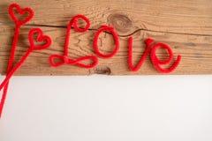 L'amour est un mot est écrit orthographiant la police Le rouge d'amour de mot Fond blanc, table en bois L'espace pour le texte Image libre de droits
