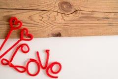 L'amour est un mot est écrit orthographiant la police Le rouge d'amour de mot Fond blanc, table en bois L'espace pour le texte Image stock
