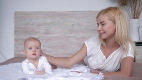 L'amour et le bonheur, jeune mère avec le bébé nouveau-né passe le temps se trouvant ensemble sur le lit et le regard in camera à clips vidéos