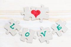 L'amour et le coeur de Word faits de morceaux de puzzle denteux sur la lumière courtisent Photographie stock