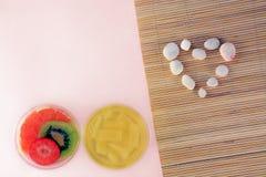 L'amour et le concept en pierre blanc de coeur avec le cotta de panna de gelée porte des fruits sur le fond en bambou rose Photographie stock