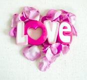 L'amour et les pétales de rose de mot sous la forme de coeur d'isolement sur le fond blanc de textile Concept de jour de Valentin Image libre de droits