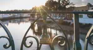 L'amour gravé ferme à clef accrocher sur un pont au-dessus d'une rivière Image stock