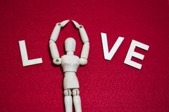 L'amour les lettres qu'en bois avec la marionnette en bois fanent dessus l'acrylique de couleur s'est senti photographie stock