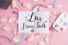 L'amour n'échoue jamais sur le fond en pastel Images stock