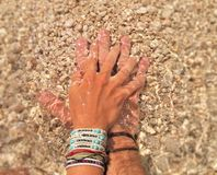 L'amour remet la plage clair comme de l'eau de roche de l'eau Photographie stock libre de droits