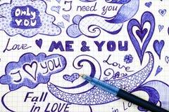 L'amour tiré par la main gribouille des messages sur le papier à carreaux avec le stylo Image libre de droits