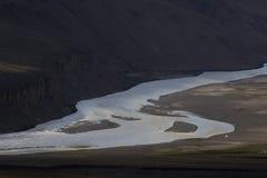L'ampio canale delle alte montagne è il fiume fra i pendii scuri della valle al tramonto, la superficie grigia dell'acqua g Fotografia Stock