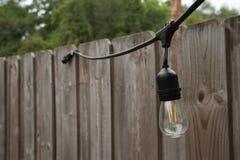 L'ampoule de réverbère sur un arbre, à l'arrière-plan est une barrière en bois image stock
