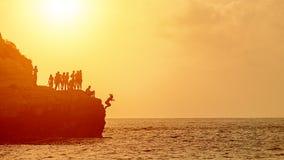 L'amusement d'été avec la falaise de meilleurs amis sautant dans l'océan, les jeunes silhouettent apprécier le temps nageant ense images stock