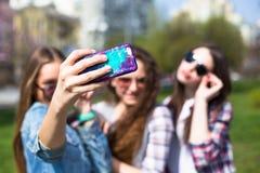 L'amusement hawing d'adolescentes heureuses passent le temps ensemble en parc de ville Image stock
