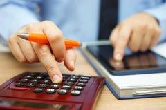 L'analista finanziario è ritorno su investimento calcolatore fotografia stock libera da diritti