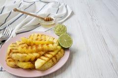 L'ananas arrostito incunea su un piatto rosa con miele e calce sopra fondo di legno bianco, vista laterale Alimento di estate clo fotografia stock libera da diritti