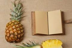 L'ananas fresco ed il taccuino che si trovano su una tela di sacco sorgono Fotografia Stock
