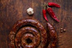 L'anello arrostito della salsiccia casalinga è su un bordo di legno con pepe ed aglio Fotografia Stock