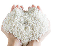 l'anello posteriore nella forma del cuore di riso bianco del grano in mano dei woman's è Fotografia Stock Libera da Diritti