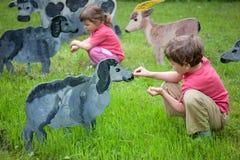 L'anf de fille les sheeps en bois d'alimentation de garçon Photos stock